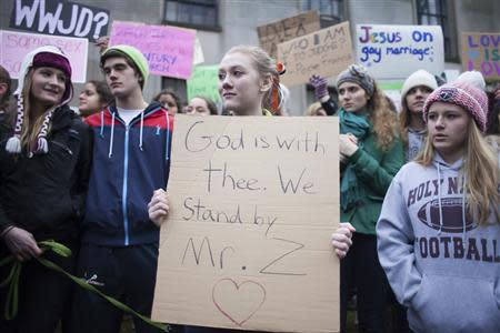An Eastside Catholic High School student holds up a sign during a rally in support of the school's former Vice Principal Mark Zmuda at the Archdiocese of Seattle chancery building in Seattle, Washington, December 20, 2013. REUTERS/David Ryder