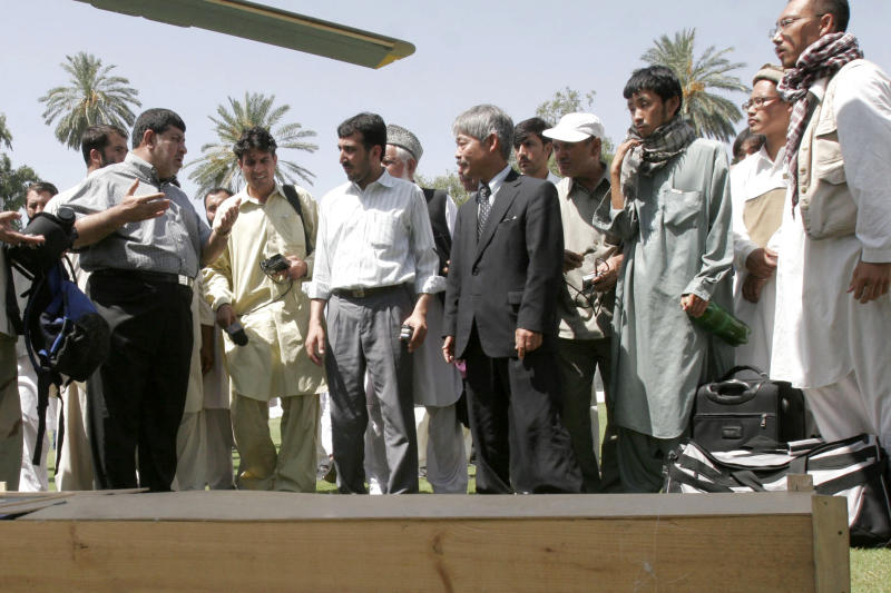 FILE -In this, Aug 28, 2008, photo, Tetsu Nakamura, center right, executive director of PMS Japan, with others, stands near the dead body of Japanese aid worker Kazuya Ito at the governor house of Jalalabad, east of Kabul, Afghanistan. The Japanese physician and aid worker in eastern Afghanistan died of his wounds after an attack Wednesday, Dec. 4, 2019, that also killed five Afghans, including the doctor's bodyguards, the driver and a passenger, a hospital spokesman said.(AP Photo/Rahmat Gul, File)