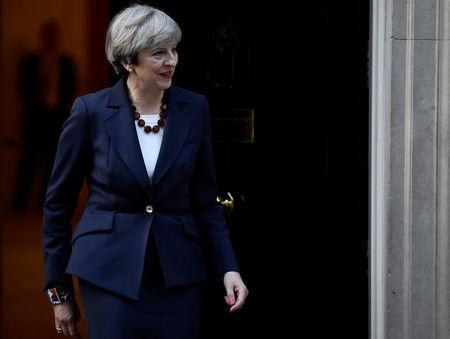 Britain's Prime Minister Theresa May walks out of 10 Downing Street to welcome Head of the European Commission, President Juncker to Downing Street in London