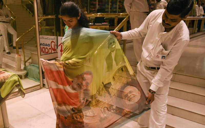 A woman tries on a saree bearing the image of Indian Prime Minister Narendra Modi  - AFP