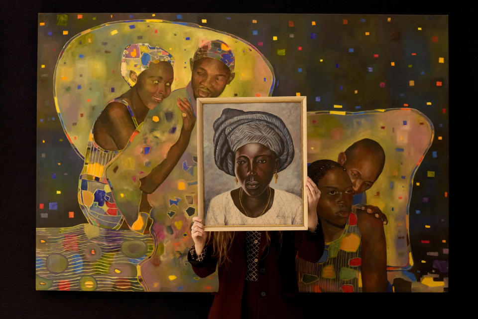 """A Bonhams employee holds a painting called """"Portrait of a Yoruba Lady"""" by Akinola Lasekan in front of a painting called """"The willing & unwilling"""" by Joseph Ntensibe at the auction rooms in London, Friday, Oct. 8, 2021. The paintings will be up for auction in Bonhams Modern and Contemporary African Art Sale on Oct. 12. (AP Photo/Kirsty Wigglesworth)"""