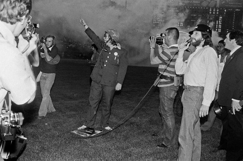 Chicago DJ Steve Dahl leads the crowd in anti-disco chants as smoke from the exploded crate of disco records lingers behind, during Disco Demolition Night, held at Comiskey Park, in between games of a nighttime doubleheader between the Chicago White Sox and the Detroit Tigers, Chicago, Illinois, July 12, 1979. (Photo: Paul Natkin/Getty Images)