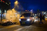 EINDHOVEN, NETHERLANDS - JANUARY 24: Police are seen near a smoldering heap of bicycles in the city centre near Eindhoven Central Station on January 24, 2021 in Eindhoven, Netherlands after a forbidden protest against the coronavirus measures turned into riots. Police cleared the area in and around Central Staition after rioters looted a supermarket and set fore to a car. (Photo by Joris Verwijst/BSR Agency/Getty Images)