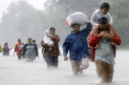 FILE PHOTO - Residents wade through flood waters from Tropical Storm Harvey in Beaumont Place, Houston, Texas, U.S., August 28, 2017. REUTERS/Jonathan Bachman