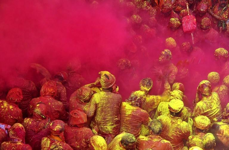 Indian Hindu devotees throw coloured powder at the Radha Rani temple during the Lathmar Holi festival in Barsana on March 21, 2013. Lathmar Holi is a local celebration, but it takes place well before the national Holi day on March 27. AFP PHOTO/ Sanjay Kanojia