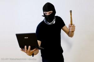 Guy with mask and hammer holding a computer
