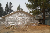FILE - In this Sept. 1, 2021 file photo Martin Diky's home completely wrapped in fire-resistant material to protect the property against the approaching Caldor Fire in Meyers, Calif. Diky decided to order $6,000 worth of aluminum protective covering to wrap his home near Lake Tahoe in June as the last big wildfire roared through the Sierra dozens of miles southwest of the forested alpine waters. (AP Photo/Jae C. Hong,File)
