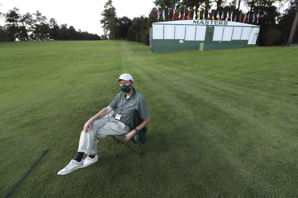 Gallery guard William E. Hardy has the course to himself while watching over the first fairway during the first practice round for the Masters golf tournament at Augusta National Golf Club, Monday, Nov. 9, 2020, in Augusta, Ga. The tournament is being played without patrons. (Curtis Compton/Atlanta Journal-Constitution via AP)