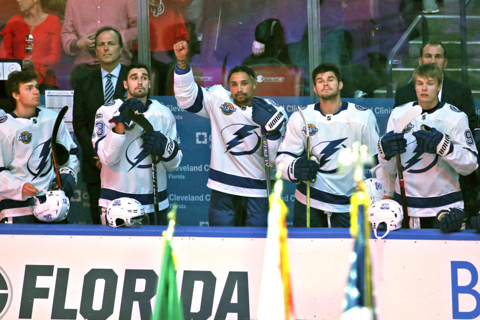 FILE - Tampa Bay Lightning right wing J.T. Brown, center, raises his fist in the air during the singing of the National Anthem before the start of an NHL hockey game between the Florida Panthers and the Tampa Bay Lightning in Sunrise, Fla., in this Saturday, Oct. 7, 2017, file photo. The Seattle Kraken has hired NHL forward JT Brown as the television analyst for its inaugural season, the team announced Monday, June 21, 2021. Brown made headlines in 2017 when he raised his fist during the national anthem during Tampa Bay's first road game in an effort to highlight racial inequality. (AP Photo/Wilfredo Lee, File)
