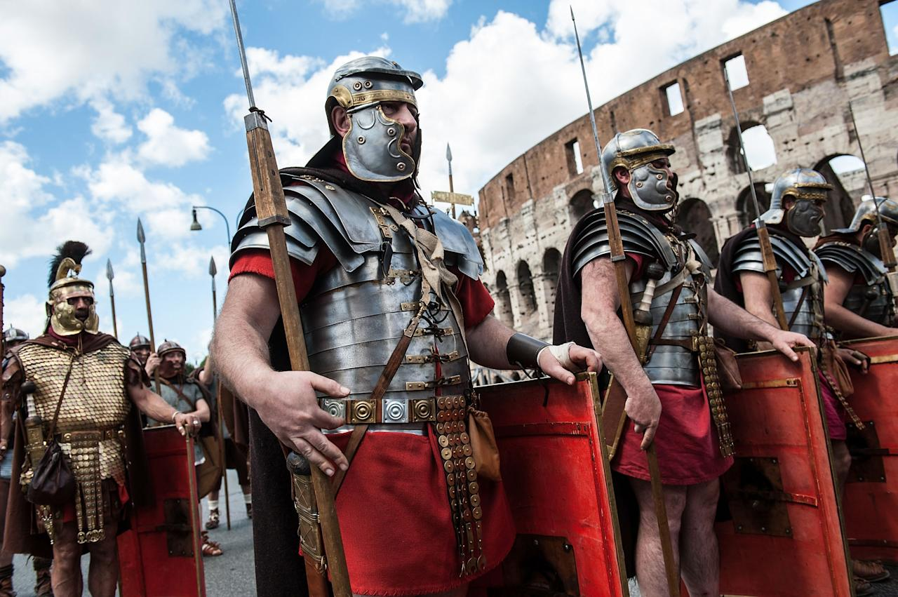 ROME, ITALY - APRIL 21: Roman soldiers march in front of the Coliseum in a commemorative parade during festivities marking the 2,766th anniversary of the founding of Rome on April 21, 2013 in Rome, Italy. The capital celebrates its founding annually based on the legendary foundation of the Birth of Rome. Actors dressed as the denizens of ancient Rome participate in parades and re-enactments of the ancient Roman Empire. According to legend, Rome had been founded by Romulus in 753 BC in an area surrounded by seven hills. (Photo by Giorgio Cosulich/Getty Images)