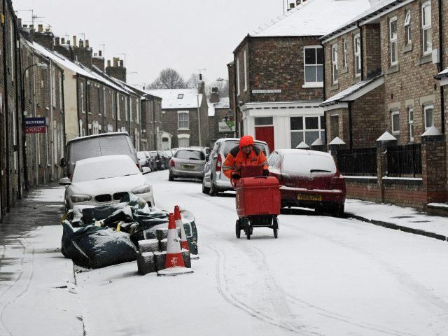 A postman makes deliveries through the snow in York (John Giles/PA)