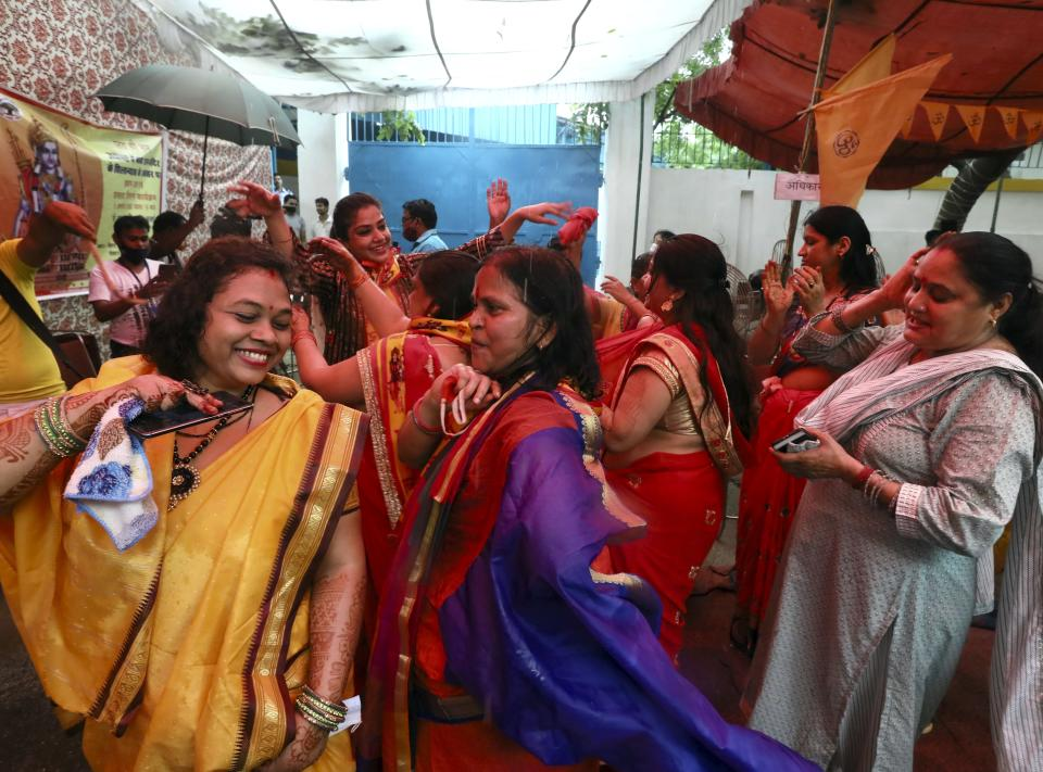 Hindu women dance to celebrate ahead of a groundbreaking ceremony of a temple dedicated to the Hindu god Ram in Ayodhya, at the Vishwa Hindu Parishad, or World Hindu Council, headquarters in New Delhi, India, Wednesday, Aug. 5, 2020. The coronavirus is restricting a large crowd, but Hindus were joyful before Prime Minister Narendra Modi breaks ground Wednesday on a long-awaited temple of their most revered god Ram at the site of a demolished 16th century mosque in northern India. (AP Photo/Manish Swarup)