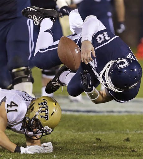 Connecticut quarterback Chandler Whitmer (10) fumbles ball as he is hit Pittsburgh's Andrew Taglianetti (41) during the first half of an NCAA college football game at Rentschler Field in East Hartford, Conn., Friday, Nov. 9, 2012. UConn recovered the ball. (AP Photo/Charles Krupa)