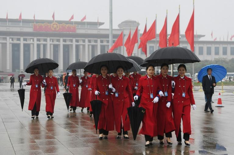 Attendants walk in Tiananmen Square as they wait for delegates during the opening ceremony of the 19th Communist Party Congress in Beijing on October 18, 2017