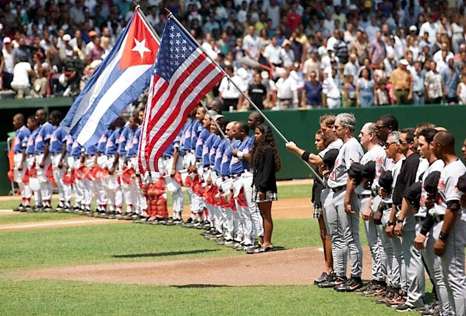 (FILES) The Baltimore Orioles (R) line up next to the Cuban national team at the Estadio Latinoamericano in Havana on March 28, 1999. It was the last occasion a US MLB team visited Cuba. It has been announced the Tampa Bay Rays will visit on March 21, 2016. (ELECTRONIC IMAGE) AFP PHOTO/Roberto SCHMIDT (AFP Photo/ROBERTO SCHMIDT)