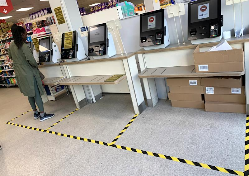 A customer stands in a taped off check-out area designed to separate shoppers in a supermarket, as the spread of coronavirus disease (COVID-19) increases, in London