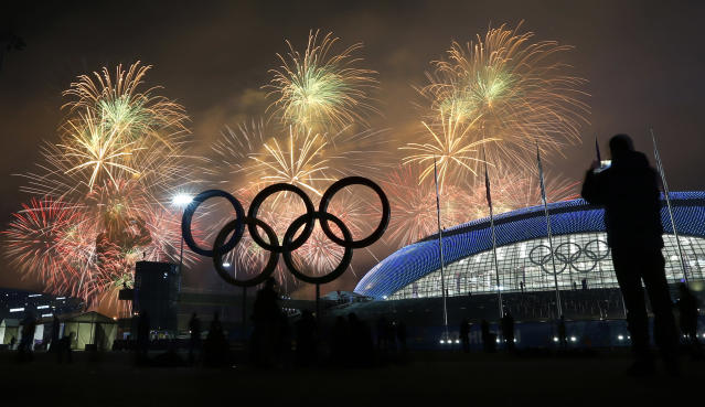 A man takes a photograph of fireworks during the closing ceremony of the 2014 Winter Olympics, Sunday, Feb. 23, 2014, in Sochi, Russia. (AP Photo/Petr David Josek)