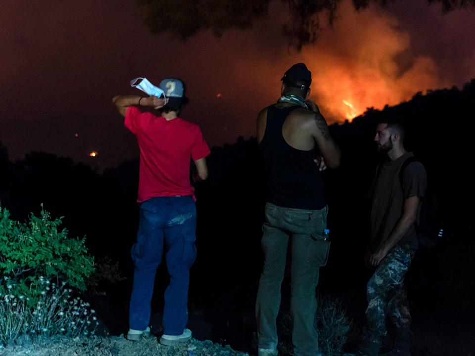 People in the village of Vavatsina watch as the wildfire rages on nearby hills (AFP via Getty Images)