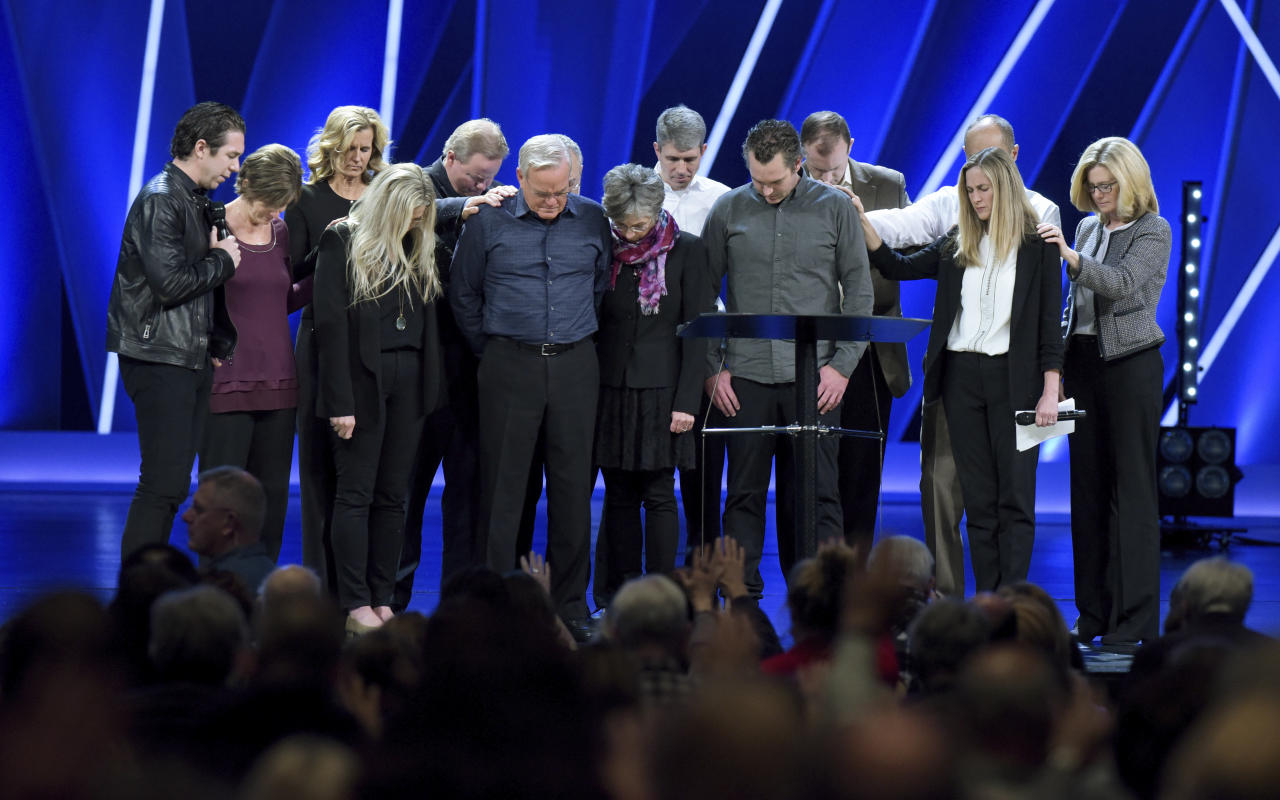 FILE - In this Tuesday, April 10, 2018 file photo, Willow Creek Community Church Senior Pastor Bill Hybels, sixth from left, and other church leaders pray before the congregation in South Barrington, Ill., where Hybels announced his early retirement effective immediately, amid a cloud of misconduct allegations involving women in his congregation. The announcement was made during a special meeting at the church, one of the nation's largest evangelical churches, which Hybels founded. (Mark Black/Daily Herald via AP)