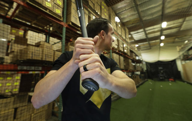 In this Feb. 8, 2018, photo, Brent Weidenbach, director of product management for Axe Bat, poses for a photo holding one of his company's baseball bats in the batting cage at the company's warehouse in Renton, Wash. Axe Bat is trying to revolutionize baseball with a simple concept -- a bat handle that is shaped like the handle of an axe. (AP Photo/Ted S. Warren)