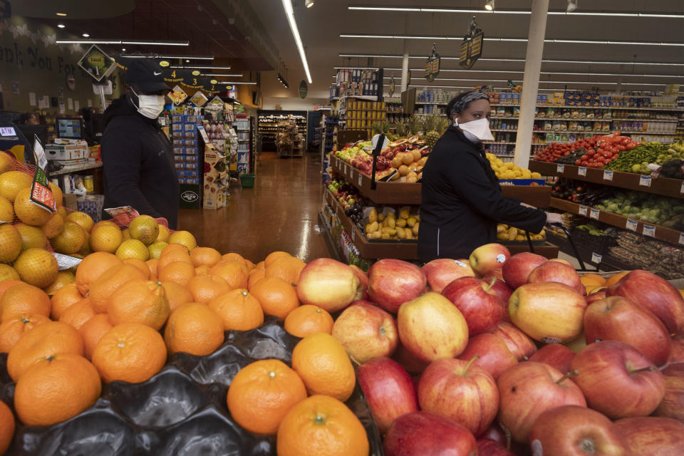A couple wearing masks looks at a selection of fruit in a Brooklyn supermarket, Wednesday, March 25, 2020 during the coronavirus pandemic in New York. The new coronavirus causes mild or moderate symptoms for most people, but for some, especially older adults and people with existing health problems, it can cause more severe illness or death. (AP Photo/Mark Lennihan)