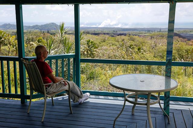 <p>Mark Clawson, 64, sits on his porch on the outskirts of Pahoa above recent lava flows during ongoing eruptions of the Kilauea Volcano in Hawaii, June 6, 2018. (Photo: Terray Sylvester/Reuters) </p>
