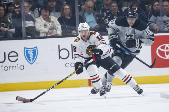 Chicago Blackhawks forward Alex DeBrincat (12) controls the puck away from Los Angeles Kings forward Anze Kopitar (11) during the first period of an NHL hockey game Saturday, Nov. 2, 2019, in Los Angeles. (AP Photo/Ringo H.W. Chiu)