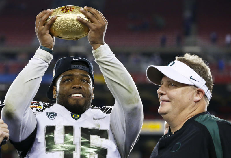 Oregon's Michael Clay, left, holds up the championship trophy as head coach Chip Kelly looks on after the Fiesta Bowl NCAA college football game against Kansas State Thursday, Jan. 3, 2013, in Glendale, Ariz.  Oregon defeated Kansas State 35-17.(AP Photo/Ross D. Franklin)