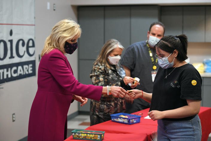 First lady Jill Biden hands a button to a woman who had just gotten his COVID-19 vaccination during a visit to First Choice Community Healthcare - South Valley Medical Center in Albuquerque, N.M., Tuesday, April 21, 2021. (Mandel Ngan/Pool via AP)