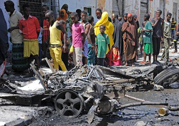 Bystanders look at the wreckage of a car bomb attack in Mogadishu on April 21, 2015 (AFP Photo/Mohamed Abdiwahab)