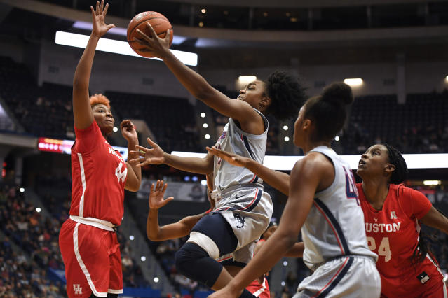 Connecticut's Christyn Williams, center, goes up for a basket as Houston's Jazmaine Lewis, left, and Houston's Maya Jones, right, defend, in the second half of an NCAA college basketball game, Saturday, Jan. 11, 2020, in Hartford, Conn. (AP Photo/Jessica Hill)