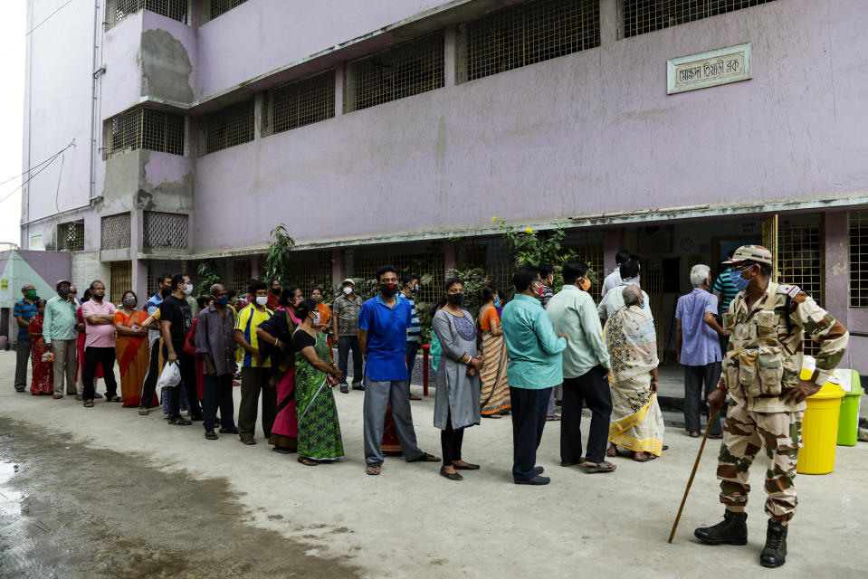 People stand in a queue to cast their votes at a polling station during the fourth phase of West Bengal state elections in Kolkata , India, Saturday, April 10, 2021. (AP Photo/Bikas Das)