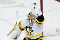 Pittsburgh Penguins goaltender Tristan Jarry gloves the puck during the second period of the team's NHL hockey game against the New Jersey Devils, Thursday, March 18, 2021, in Newark, N.J. (AP Photo/John Minchillo)