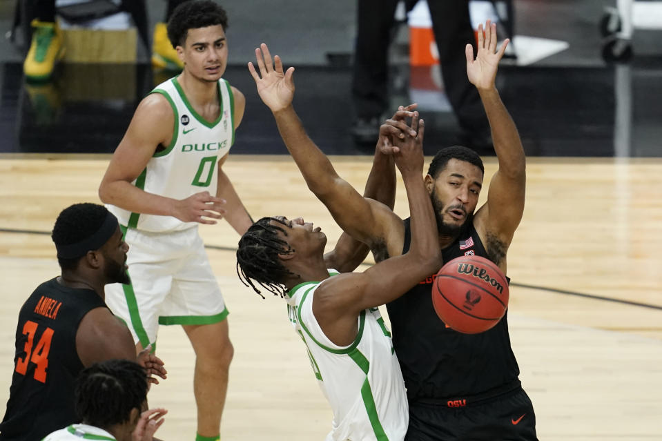 Oregon State's Maurice Calloo, right, fouls Oregon's Eric Williams Jr. (50) during the first half of an NCAA college basketball game in the semifinal round of the Pac-12 men's tournament Friday, March 12, 2021, in Las Vegas. (AP Photo/John Locher)