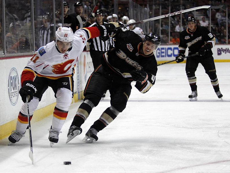 Calgary Flames center Mikael Backlund (11), of Sweden, races to the puck with Anaheim Ducks defenseman Hampus Lindholm (47), of Sweden, during the first period of an NHL hockey game, Wednesday, Oct. 16, 2013, in Anaheim, Calif. (AP Photo/Alex Gallardo)