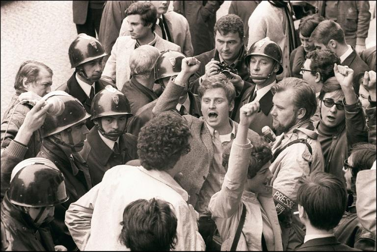 "Student leader Daniel Cohn-Bendit (centre, with fist raised) sings the left-wing anthem ""The Internationale"" with other students and facing the security forces on May 6, 1968"