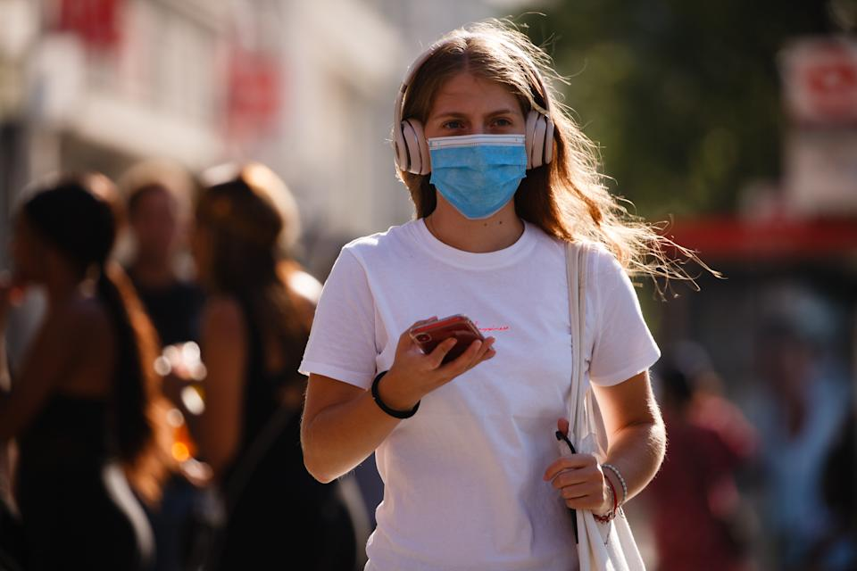 A woman wearing a face mask waits at a pedestrian crossing on Oxford Street in heatwave conditions in London, England, on June 25, 2020. Temperatures rose to 33C in parts of London today, in what has been one of the UK's hottest days of the year so far. Central London was nonetheless busy with shoppers this afternoon as the retail sector mounts its comeback after coronavirus lockdown restrictions on non-essential shops were eased at the beginning of last week. Among retailers, confidence is reportedly low that recovery will be swift, however, with a survey from the Confederation of British Industry (CBI) today revealing fears of reduced consumer demand as well as operational challenges such as staff absences and transport difficulties. (Photo by David Cliff/NurPhoto via Getty Images)