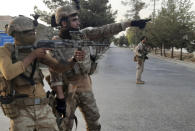 Afghan Special forces patrol a deserted street during fighting with Taliban fighters, in Lashkar Gah, Helmand province, southern Afghanistan, Tuesday, Aug. 3, 2021. The Taliban pressed ahead with their advances in southern Afghanistan on Tuesday, capturing nine out of 10 districts of the Helmand provincial capital, residents and officials said. The fall of Lashkar Gah would be a major turning point in the offensive the Taliban have waged over the past months as U.S. and NATO forces complete their pullout from the war-torn country. (AP Photo/Abdul Khaliq)