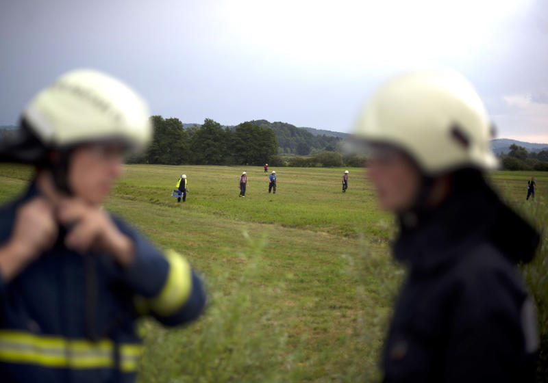Rescuers survey the site of a hot air balloon crash near Ljubljana, Slovenia, Thursday, Aug. 23, 2012. A hot air balloon carrying 32 people, including children, was swept up in a storm and crashed in a fireball outside Slovenia's capital on Thursday, killing four people and 28 injured were taken to hospital, police and doctors said. The cause of the accident was not immediately clear. (AP Photo/Matej Leskovsek)