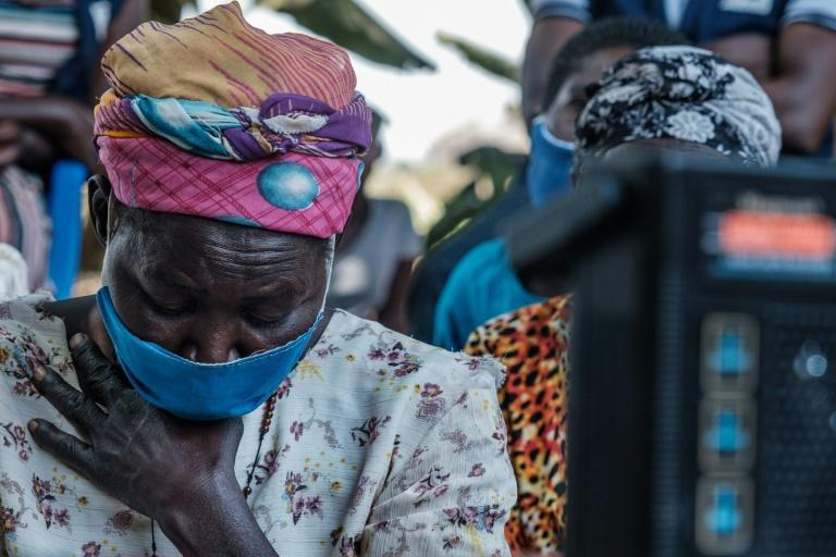 Verdict: Thousands of kilometres (miles) from The Hague, a woman in Lukodi listens to the ruling of the International Criminal Court