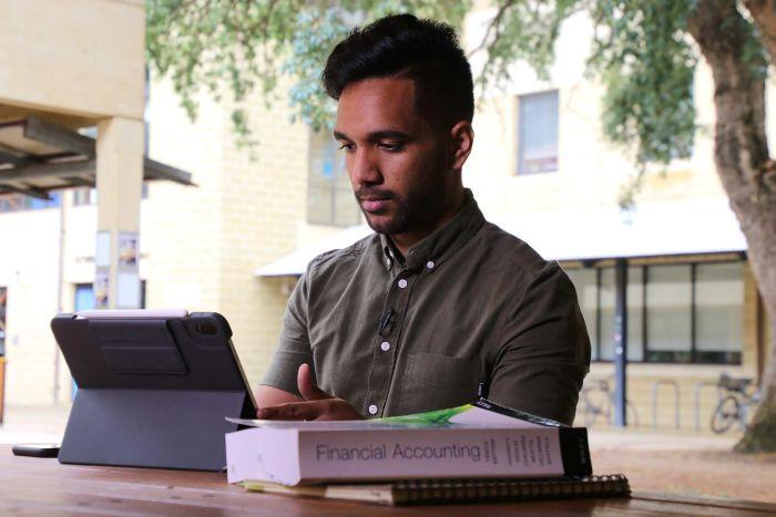 A mid-shot of a man sitting at an outdoor table studying on a tablet with books on the table.