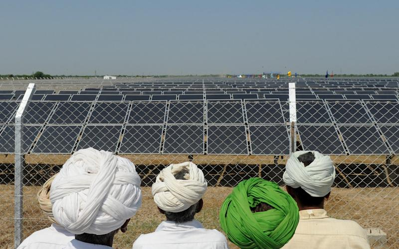 Indian villagers look at solar panels during the inauguration of a solar farm in the village of Gunthawada, Banaskantha district, some 175kms. from Ahmedabad on October 14, 2011. - Credit: AFP