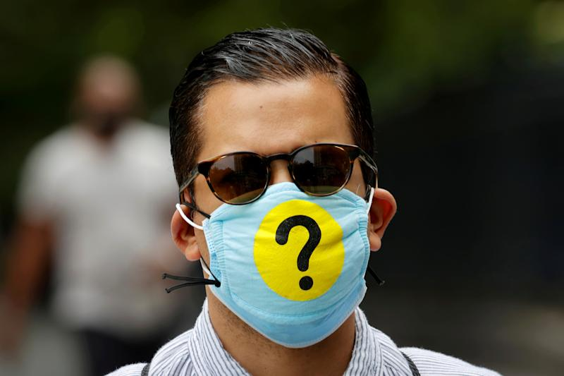 A man wears a protective face mask decorated with a question mark in lower Manhattan during the outbreak of the coronavirus disease (COVID-19) in New York, U.S., May 22, 2020. Picture taken May 22, 2020. REUTERS/Mike Segar TPX IMAGES OF THE DAY
