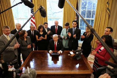 President Trump signs an executive order cutting regulations, accompanied by small business leaders at the Oval Office of the White House. REUTERS/Carlos Barria