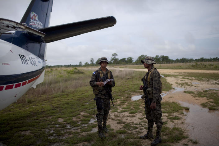 ADVANCED FOR USE SUNDAY FEB. 3 AND THEREAFTER FILE - In this Monday, May 21, 2012 file photo, Honduran soldiers stand next to a plane after checking passengers information in Brus Laguna, Honduras. On Friday May 11, a joint Honduran-U.S. drug raid, on a helicopter mission with advisers from the DEA, appears to have mistakenly targeted civilians in the remote jungle area, killing four riverboat passengers and injuring four others. The incident drew international attention and demands for investigation when the DEA confirmed it had agents aboard the helicopters advising their Honduran counterparts. Villagers spoke of English-speaking commandos kicking in doors and handcuffing locals just after the shooting, searching for drug traffickers. (AP Photo/Rodrigo Abd, file)