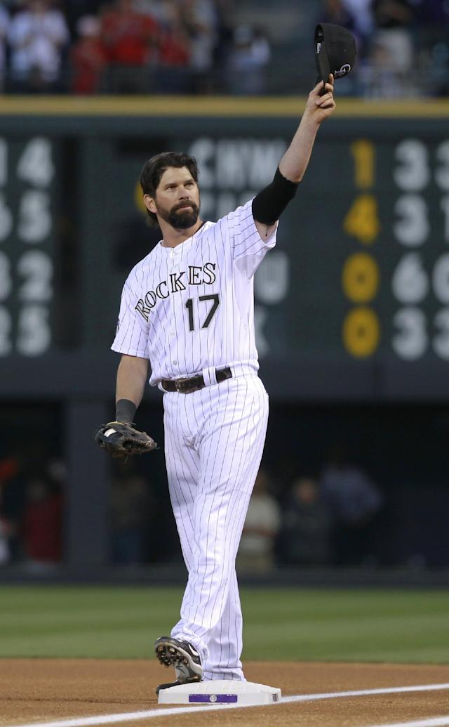 Colorado Rockies first baseman Todd Helton doffs his cap to the crowd as he takes his position on the diamond to face the Boston Red Sox in the first inning of a baseball game in Denver on Wednesday, Sept. 25, 2013. Helton, who will retire at season's end, was playing in his final home game after 17 years at first base for the Rockies. (AP Photo/David Zalubowski)