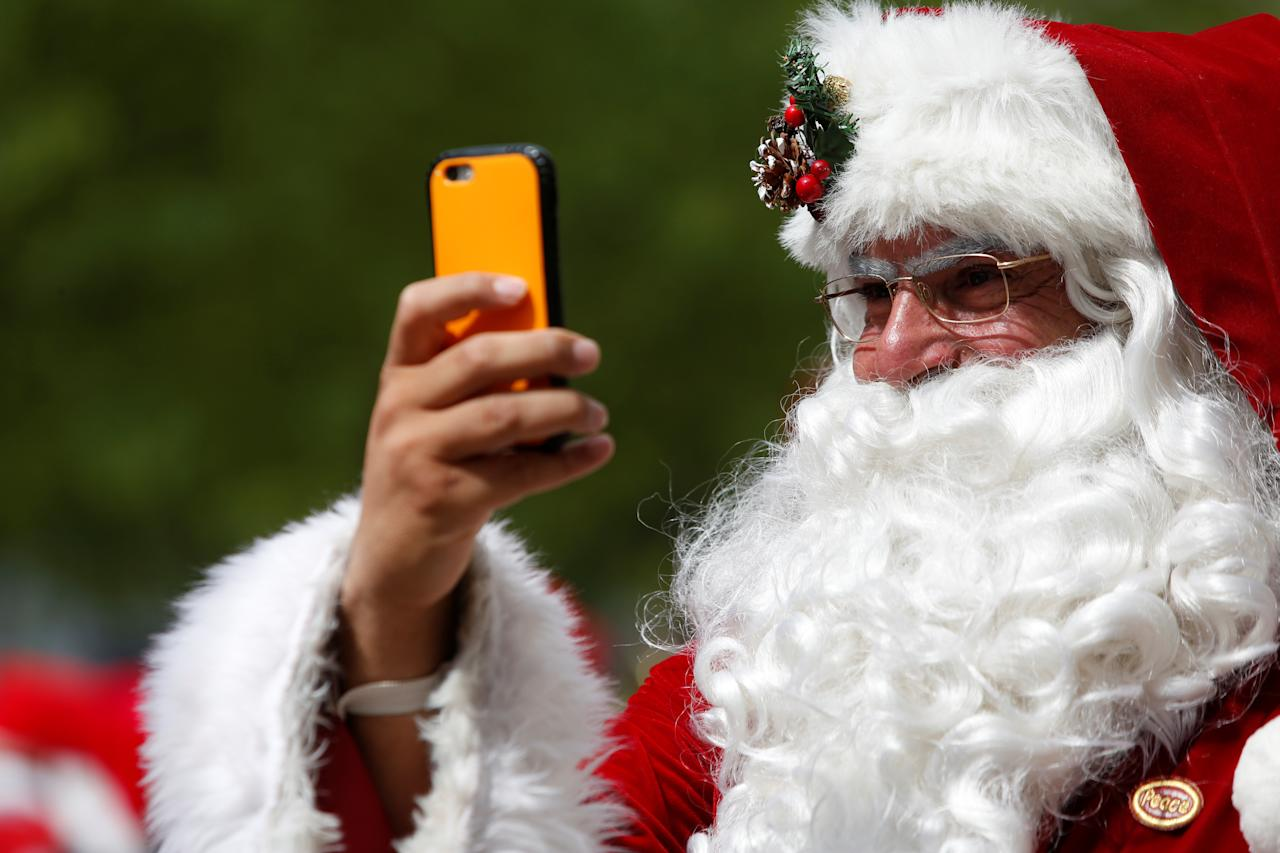 <p>A man dressed as Santa Claus records on his cellphone as he takes part in the World Santa Claus Congress, an annual event held every summer in Copenhagen, Denmark, July 23, 2018. (Photo: Andrew Kelly/Reuters) </p>