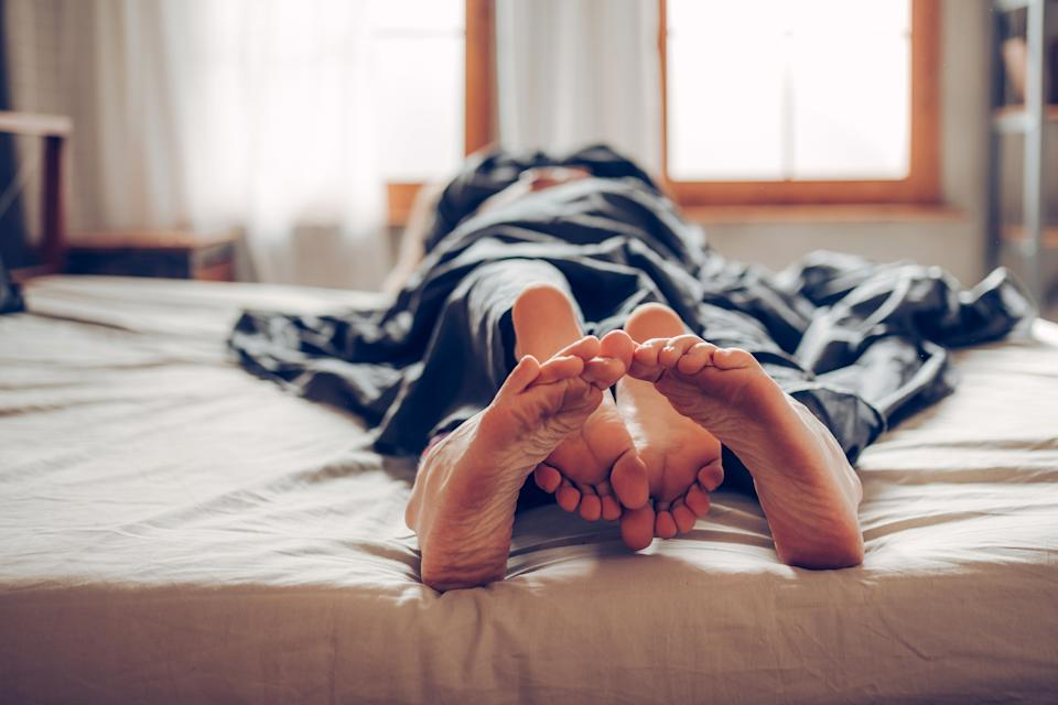 Adult couple's feet looking out of bed. Photo: Getty Images.