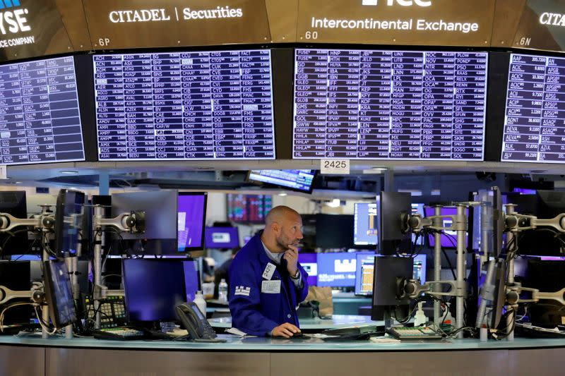 FILE PHOTO: FILE PHOTO: A trader works on the trading floor at the New York Stock Exchange (NYSE) in Manhattan, New York City