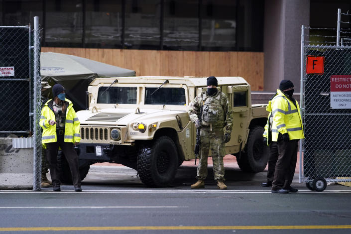 A National Guard soldier stands guard with deputies at the restricted vehicle entrance of the building where the Chauvin trial is being held. (Jim Mone/AP)